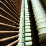 Photo looking down along the strings of an upright piano.