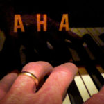 Photo of Yamaha piano with only the 'AHA' showing.