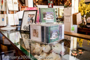 Jim Gibson's solo piano CDs displayed on a counter in a gift shop.